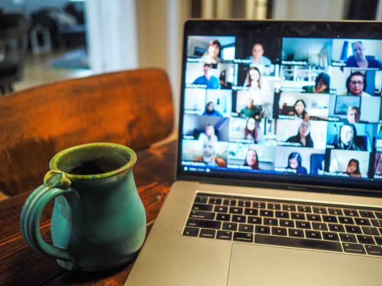 Laptop with video call and a coffee mug